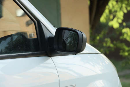 one big black plastic car mirror next to the gray glass of a white passenger auto on the street