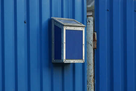 one blue iron mailbox hanging on a metal fence wall