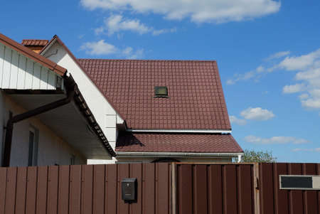 part of a brown tiled roof of a private house with one window behind a metal fence against a blue sky