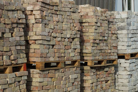 a pile of brown and white bricks on wooden pallets in the street