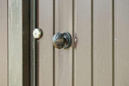 one round black iron door handle on brown metal door outside