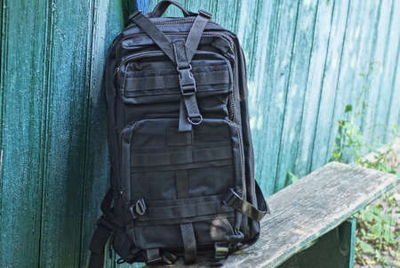 one black tactical backpack stands on a gray wooden bench against a green wall on the street