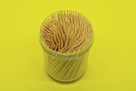 a set of sharp brown wooden toothpicks in a plastic box stands on a yellow table