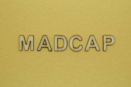 word madcap made from wooden letters lies on a yellow table Stock Photo