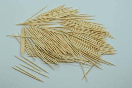 a lot of brown sharp wooden toothpicks lie in a heap on a white table