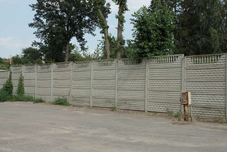 long private concrete gray fence wall on a rural street Stock Photo