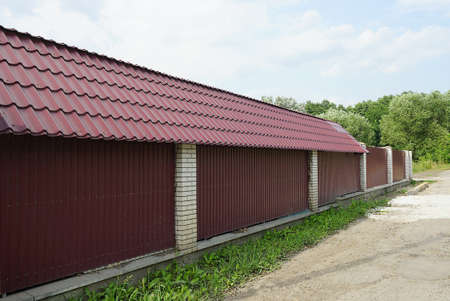red tiled roof of a house behind a  metal and white bricks fence wall against a blue sky Stock Photo