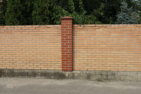 part of a brown wall of a brick fence on the street on gray asphalt Stock Photo