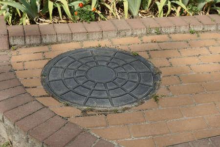 one black iron manhole lying on a brown sidewalk outside