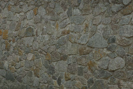 gray brown texture of stones in the wall of the fence on the street