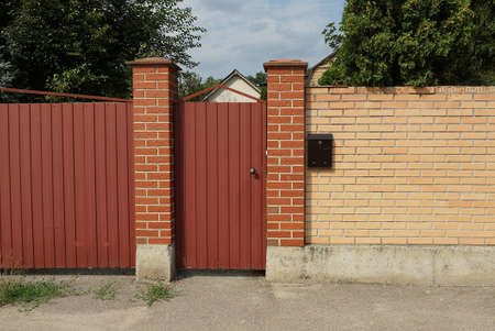 one red closed metal door on a brown brick wall of a fence on the street Stock Photo