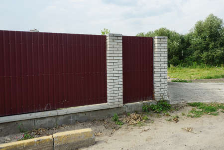 part of a private wall of a fence made of red metal and white bricks on a rural street Stock Photo