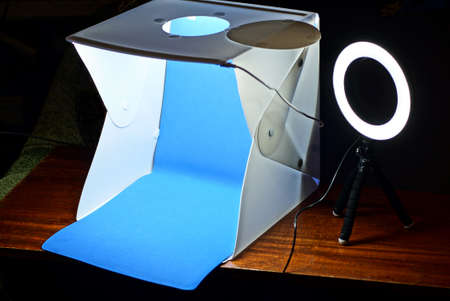 a white plastic lightbox with a blue background and a selfie ring lamp on a tripod Stock Photo