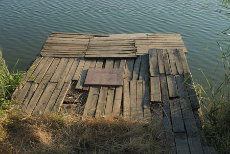 one large gray wooden bridge in the water and on the shore of a reservoir in green vegetation and grass Stock Photo