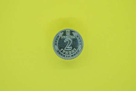 one new gray coins of Ukraine two hryvnia lies on a yellow table Stock Photo