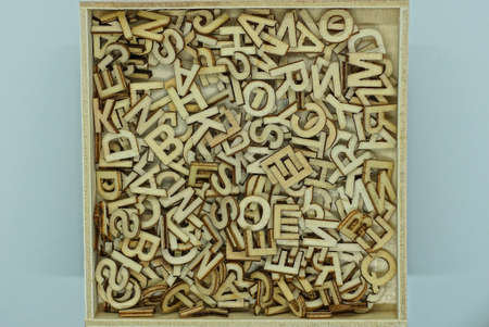pile of small brown gray wooden letters lie in a square box on a gray table Stock Photo