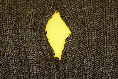 black background of fabric from torn clothes with a yellow hole Stock Photo