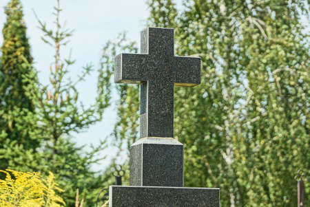 one black stone cross on the monument at the grave in the cemetery against a blue sky and green tree branches