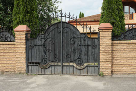one large black metal gate with an iron wrought iron pattern and sharp rods against a brown brick wall of a fence on a rural street Stock Photo