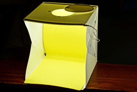 one white square plastic box with lighting for product photography with yellow background on a brown table against a black wall