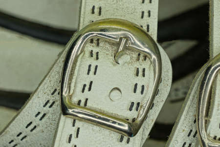 white leather harness with a gray metal fastener on a dirty sandal