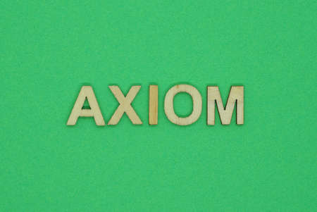 gray word axiom from small wooden letters on a green table