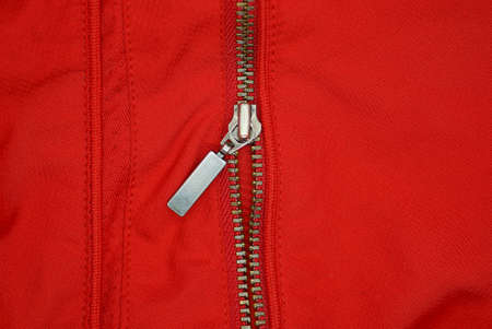 one gray metal open zip on a red fabric of clothing