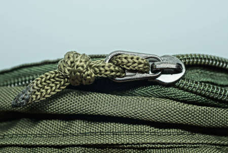 one gray metal zip with a drawstring on a green fabric of a backpack on a white background