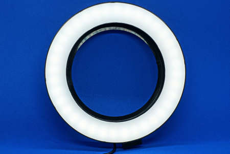 one white large round lamp selfie ring against the blue wall
