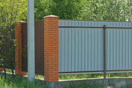 corner wall of a fence made of red bricks and brown gray metal on the street in green vegetation