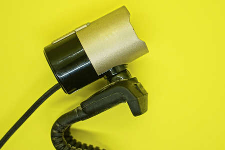 one small plastic black brown webcam lies on a yellow table