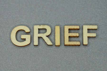 text the word grief from gray wooden small letters on an gray table