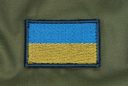 one rectangular blue yellow patch of the Ukrainian flag on the green fabric of the backpack Stock Photo