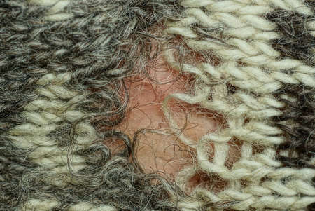 part of an old woolen sweater made of gray white fabric with a large ragged hole