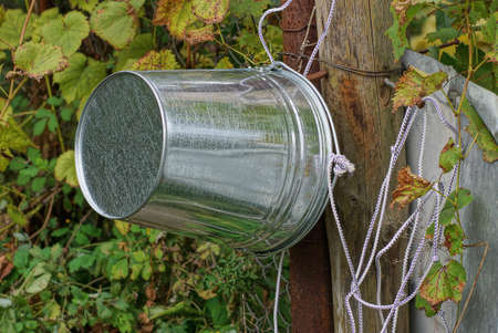 one gray metal zinc bucket hangs on a wooden pole with a white rope near a well among green vegetation on the street