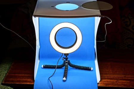 a white plastic lightbox with a blue background and a selfie ring lamp on a tripod stand on a brown table on a black background Stock Photo