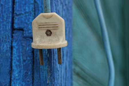 one old white electrical plug on a wire hanging on a blue wooden wall Stock Photo