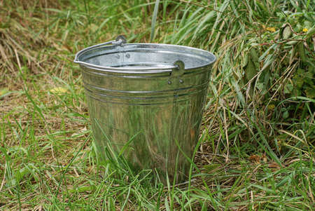 one gray large galvanized metal bucket stands outside in the green grass Stock Photo