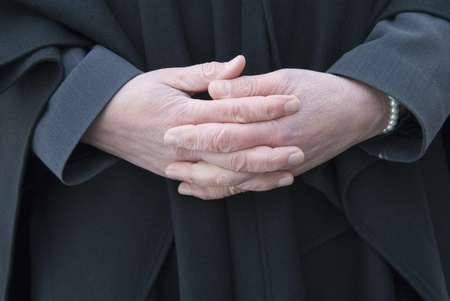 A female funeral leader is respectfully folding her hands