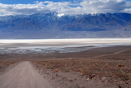 The bottom of a dry lake, mountains with snow, and a road in front in Death Valley Stock Photo - 9075207