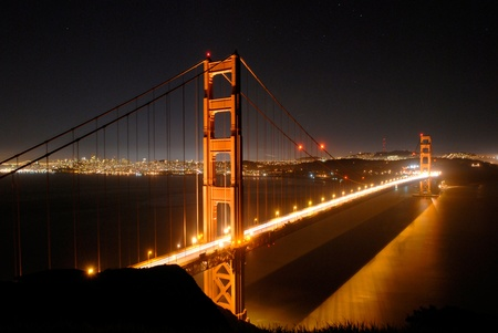 cable bridge: The Golden Gate Bridge after sunset with the lights of San Francisco in the background