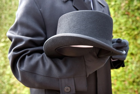 A funeral leader is respectfully carrying his hat