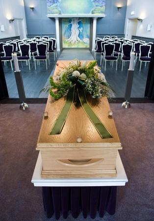 Ein Sarg mit ein Blumenarrangement an einer Leichenhalle