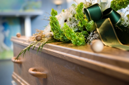 trumna: A coffin with a flower arrangement at a mortuary