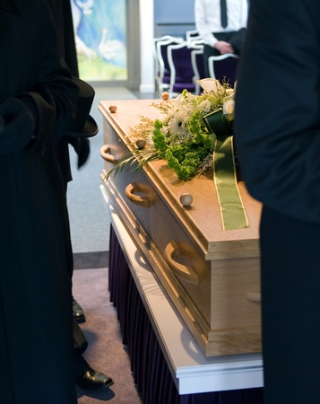 A coffin with a flower arrangement and bearers at a mortuary