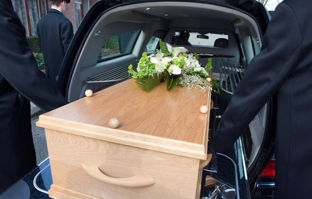 crematorium: Bearers are carrying a coffin in a mourning car Stock Photo