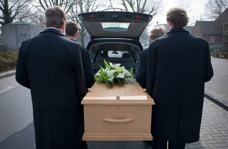coffins: Bearers are carrying a coffin out of a mourning car