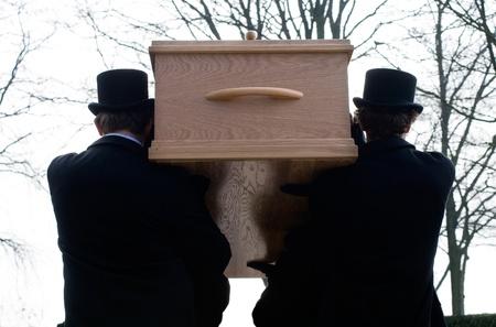 Träger sind einen Sarg zu einem Friedhof tragen