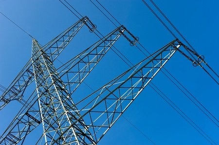 Part of an electricity pylon with blue sky on the background Stock Photo