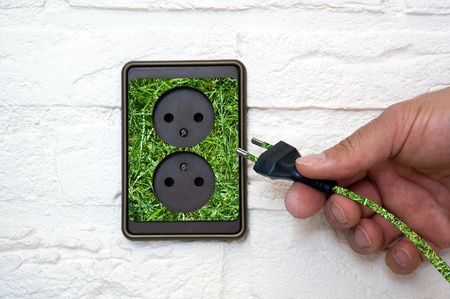 Green energy coming out of an outlet photo